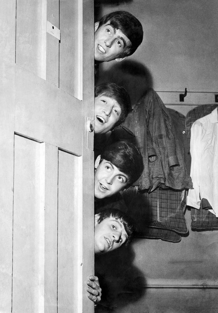 The Beatles peering out from behind their dressing room door before a performance in Manchester