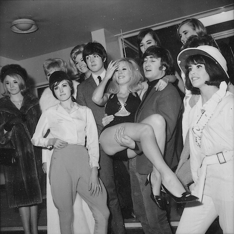 Beatles Paul McCartney and John Lennon pictured with showgirls