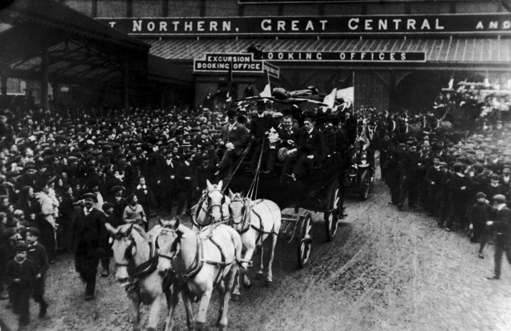 Manchester united at central station showing off their trophy to cheering crowds in 1909
