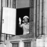 The Queen waves from the first floor window of The Manchester Town Hall