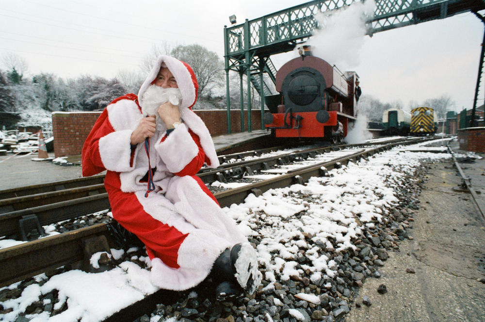Father Christmas sitting on railway tracks.