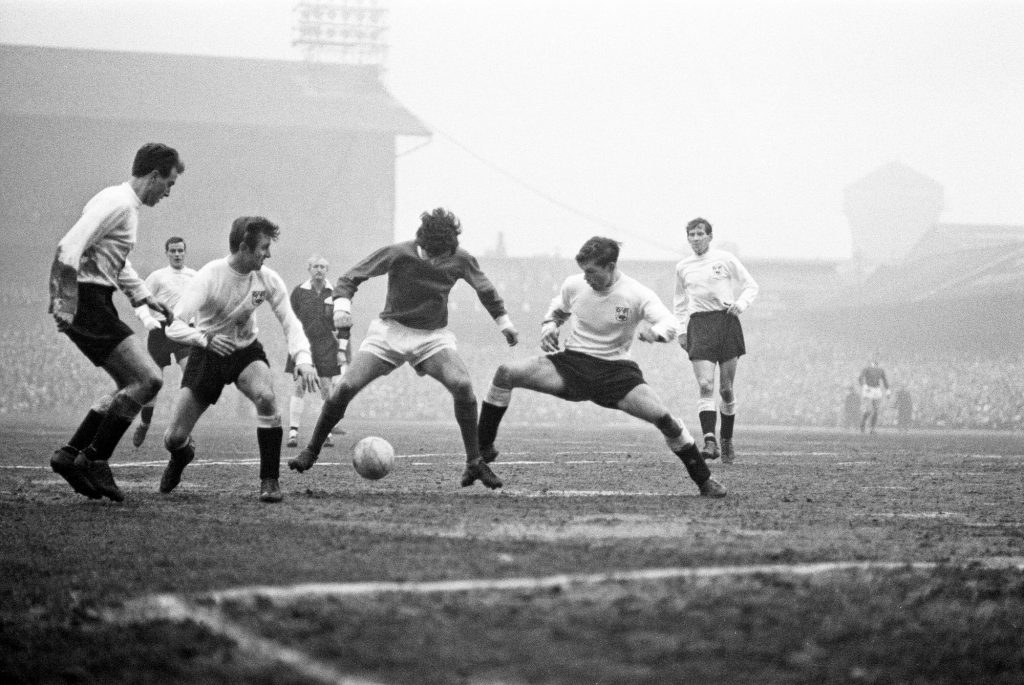 George Best in action to beat three defenders