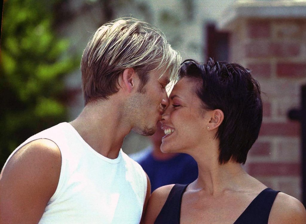David Beckham and Victoria Adams, pictured in a romantic kiss outside their home