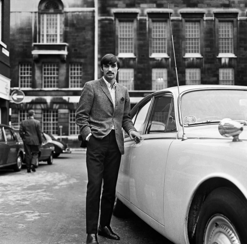 Manchester United footballer George Best beside his car.