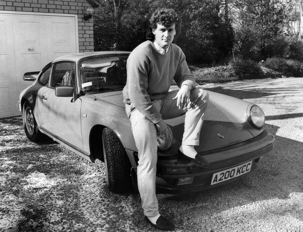 Manchester United footballer Mark Hughes poses with his car