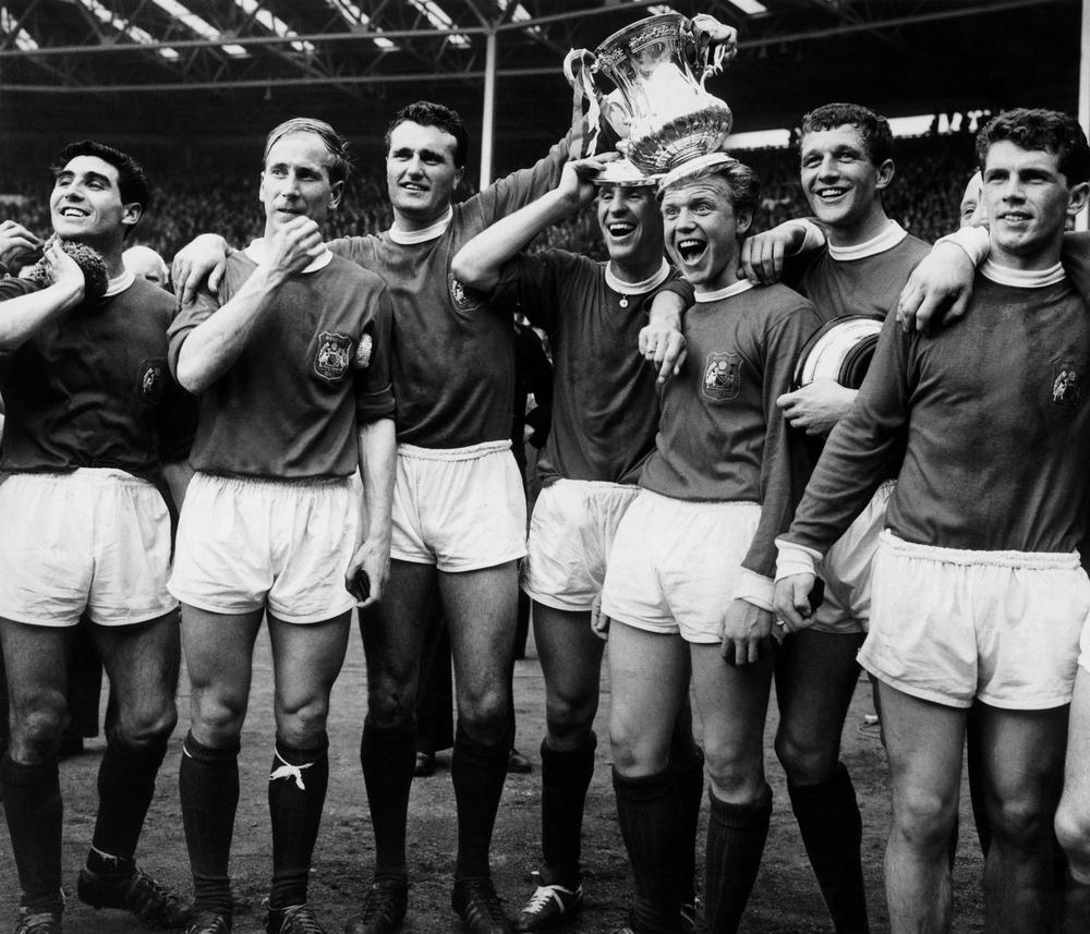 Tony Dunne, Bobby Charlton, Noel Cantwell, Pat Crerand, Albert Quixall, David Herd and Johnny Giles celebrate with the trophy after the match.