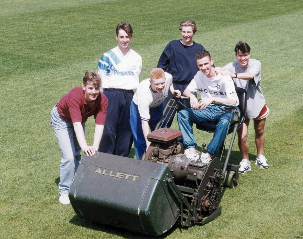 Manchester United youth team players surrounding a lawnmower on the pitch