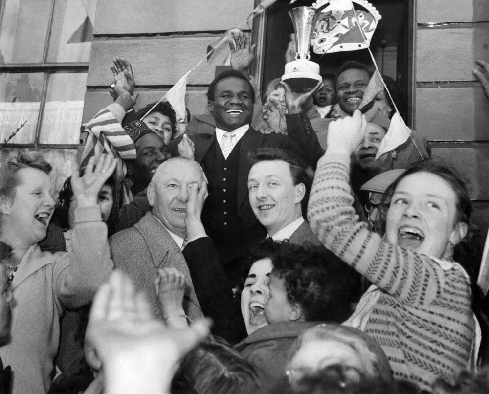 World champion Hogan Bassey is cheered by neighbours at his mother-in-law's house in Carter Street, Liverpool, April 1958