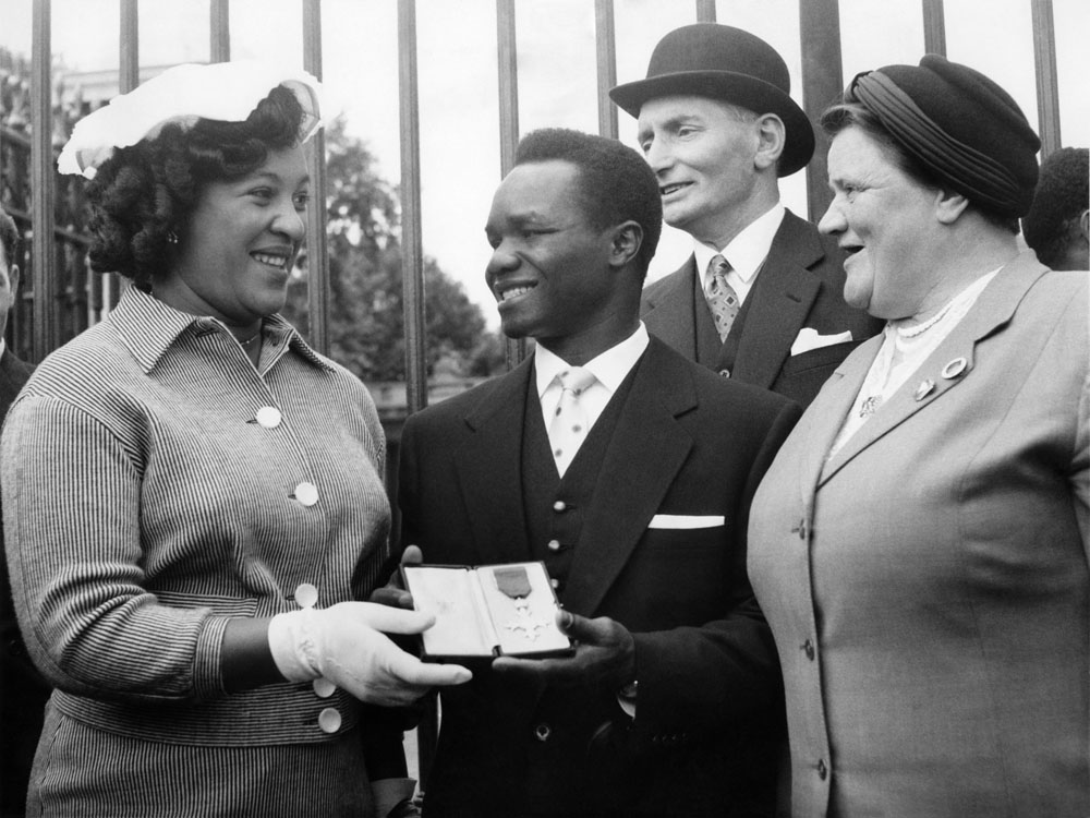 Liverpool boxer Hogan Bassey receives the MBE at Buckingham Palace with his wife Maria, left, and city MP Bessie Braddock, July 1958