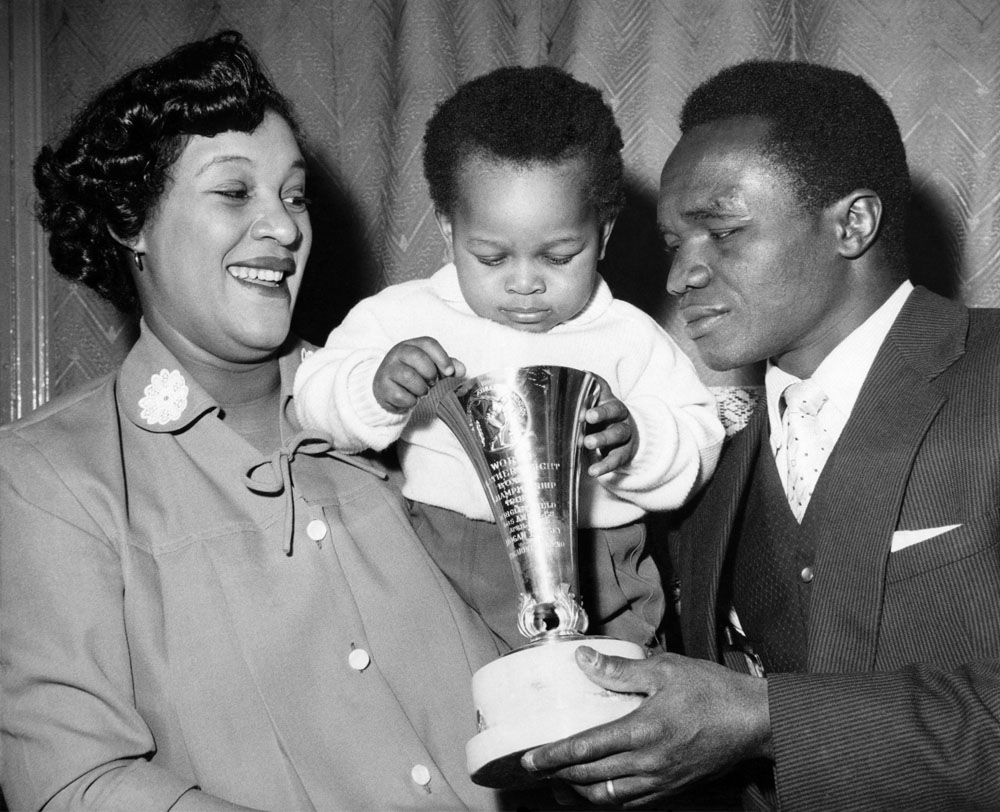 Boxer Hogan Bassey with wife Maria and son Hogan Junior, who's taking a close look at Dad's world featherweight trophy, April 1958