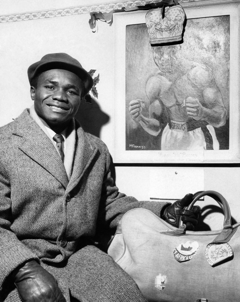 Bags packed ready for his next bout, modest world champion Hogan Bassey sits under his portrait at his Liverpool training HQ, January 1958