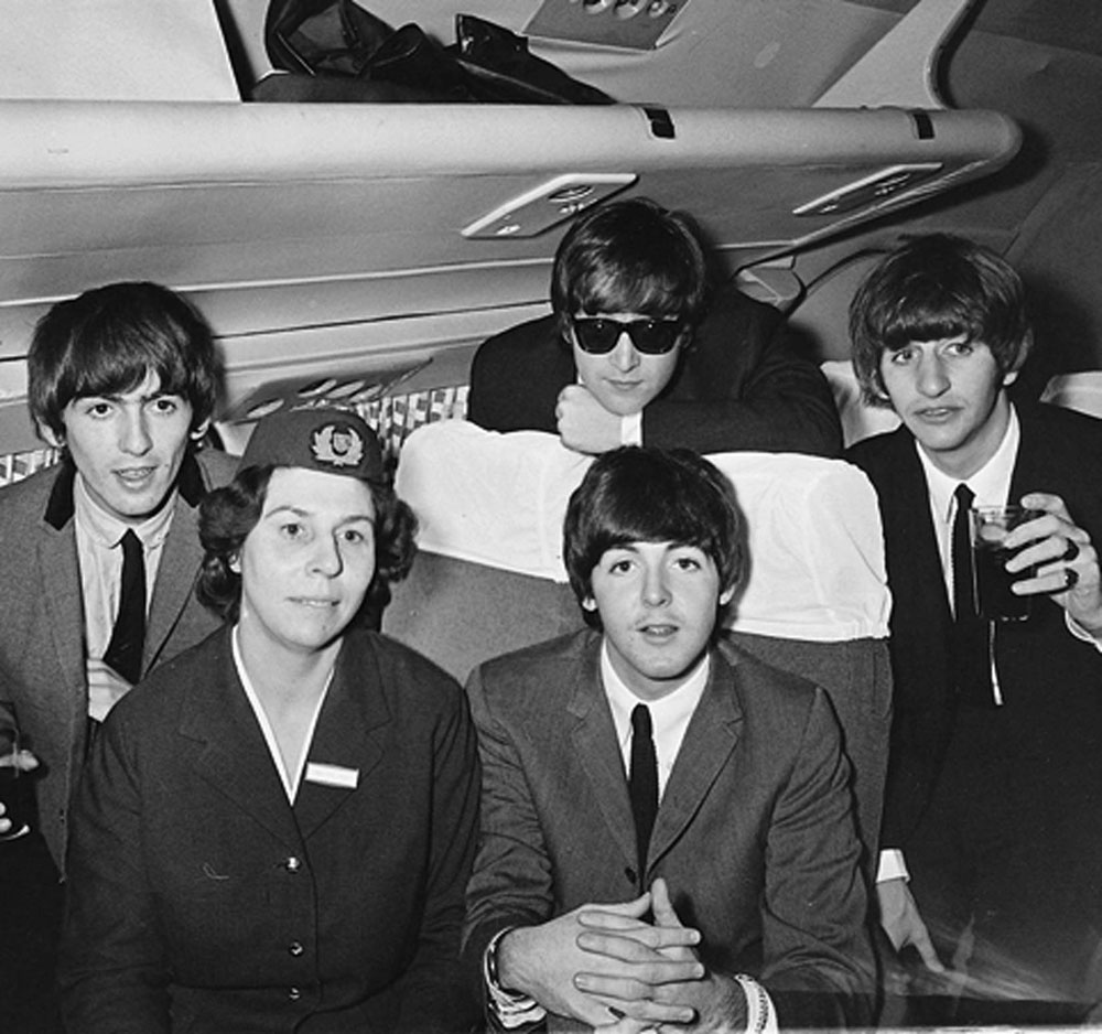 The Beatles on the plane to Speke airport for the Liverpool premiere of their film A Hard Day's Night, July 1964