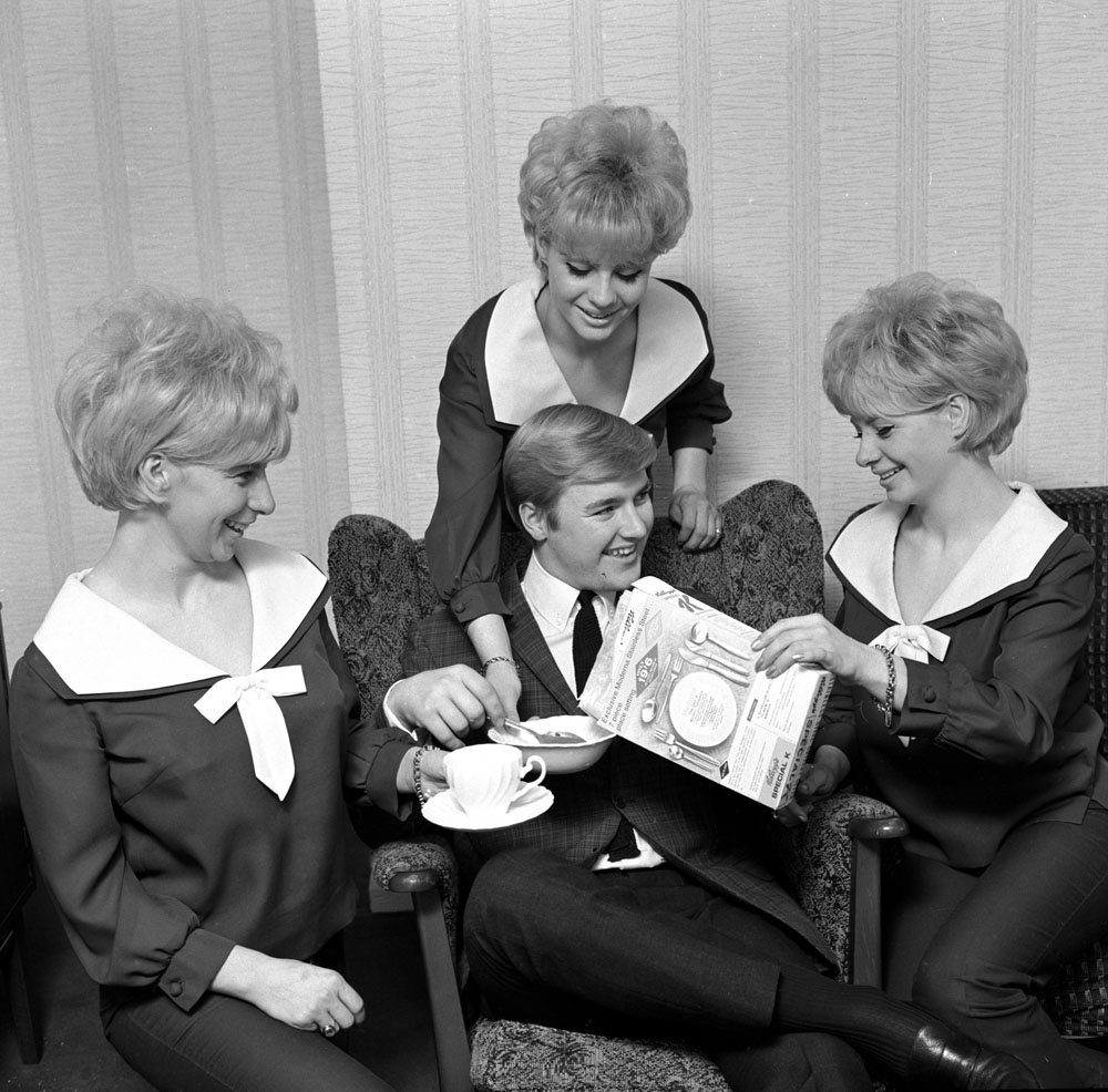 Bell sisters Jean, Carol and Sue serve cereal to Alan David, the singing compere of the BBC TV series Gadzooks, It's in the Crowd, June 1965