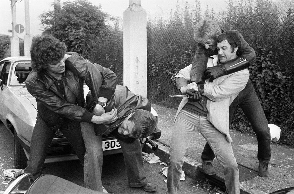 TV crime-busters The Professionals, Lewis Collins and Martin Shaw, are not impressed that someone has smashed the windscreen of their Ford Capri, June 1979