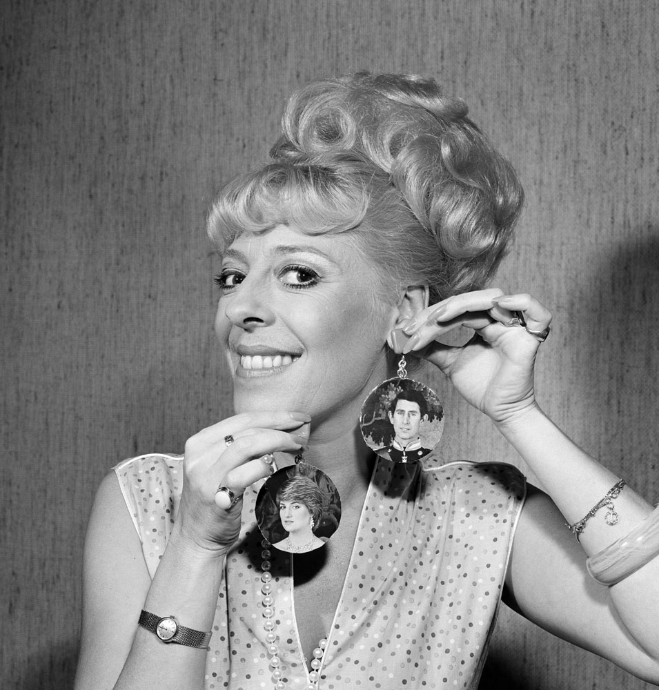 Julie Goodyear, Bet Lynch in Coronation Street, displays her Charles and Diana earrings, May 1982