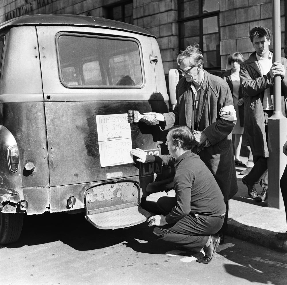 Union officials paste a notice on the back of a van to say the national strike is still on, May 1966