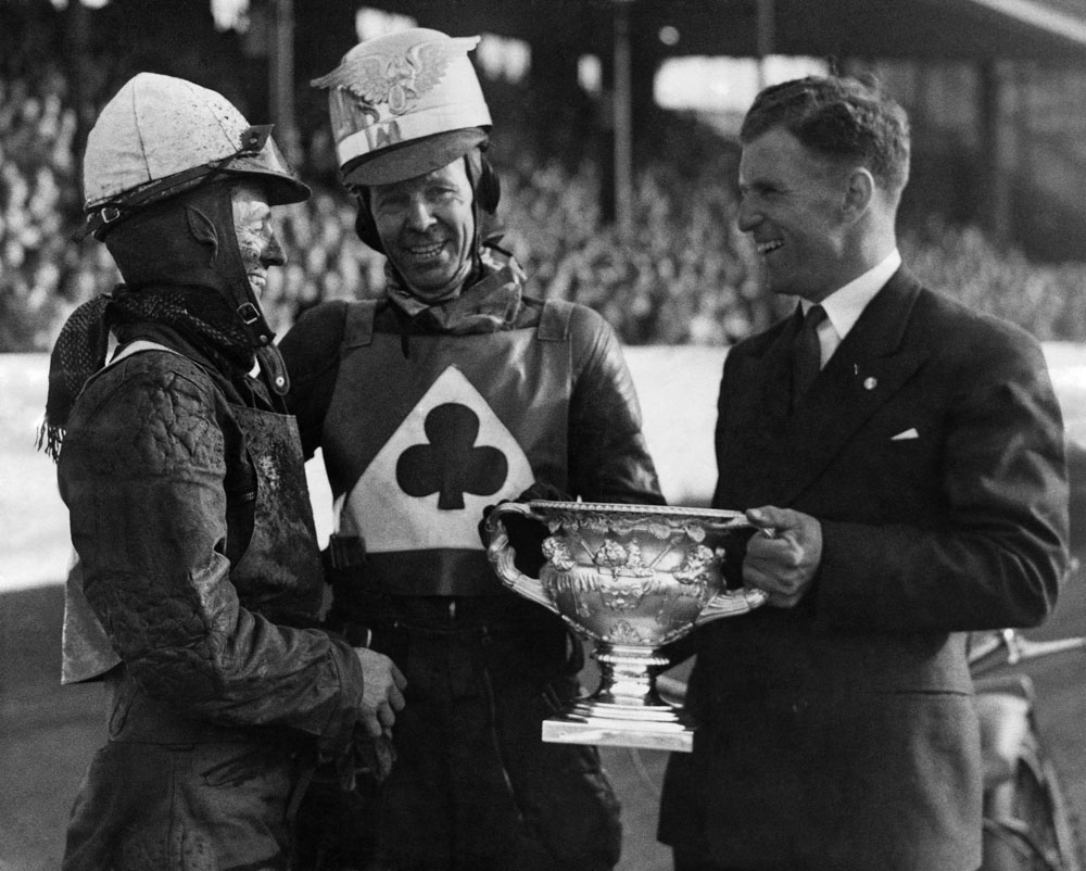 United footballer Jack Rowley presents rider Jack Parker with his race trophy. Gallant loser Aub Lawson is on the left, July 1949