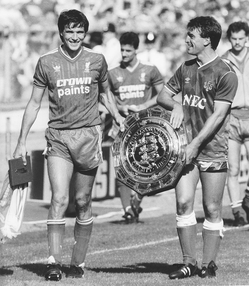 Liverpool's Alan Hansen and Everton's Kevin Ratcliffe share the Charity Shield after the 1-1 draw at Wembley, August 1986