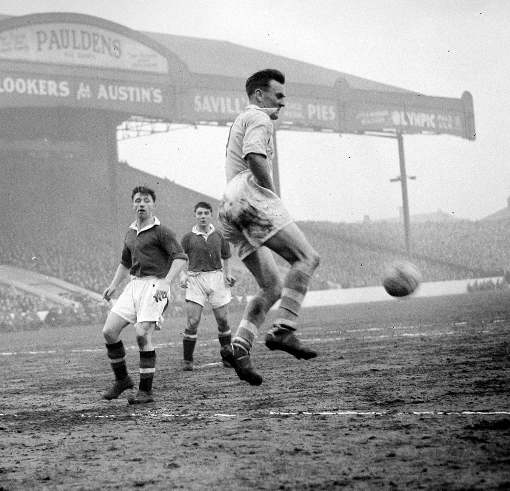 City's Don Revie clears the ball during an FA Cup tie watched by Roger Byrne and Duncan Edwards of United, January 1955