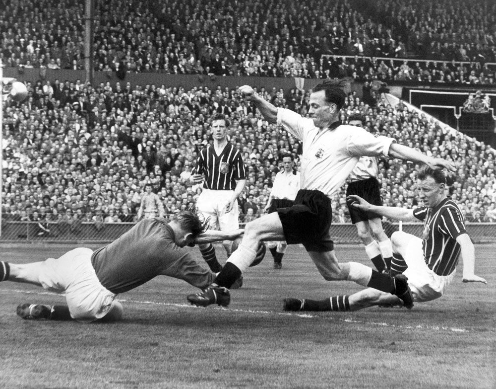 Trautmann dives at the feet of Birmingham's Peter Murphy during the 1956 FA Cup Final.