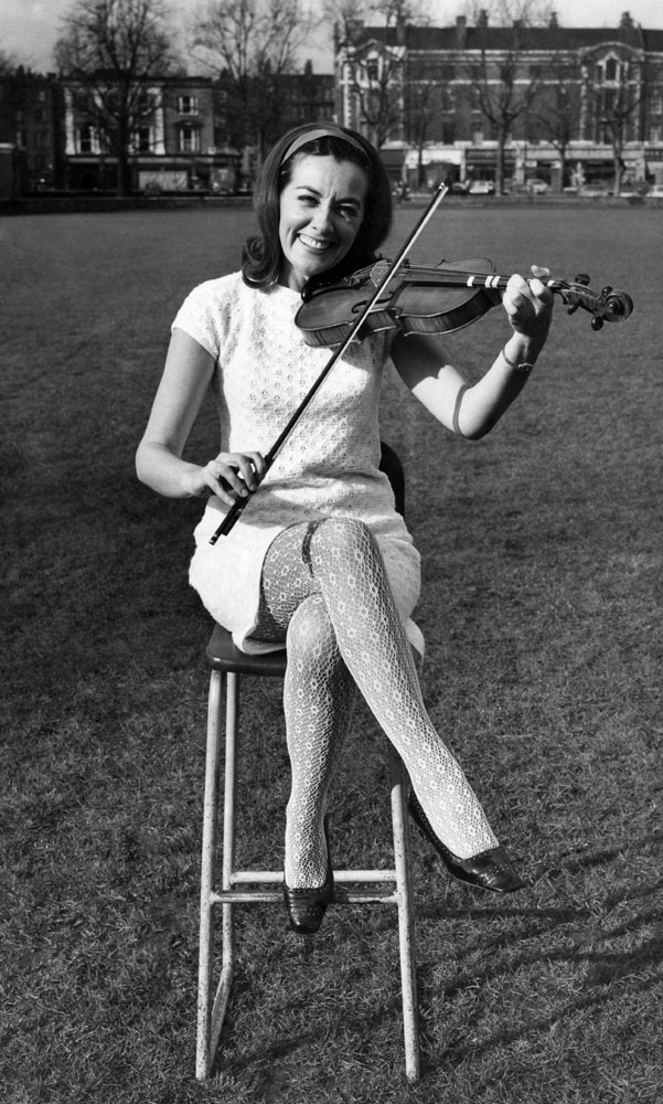 Singer and dancer Anne Rogers tunes up for stage role with a violin, February 1968