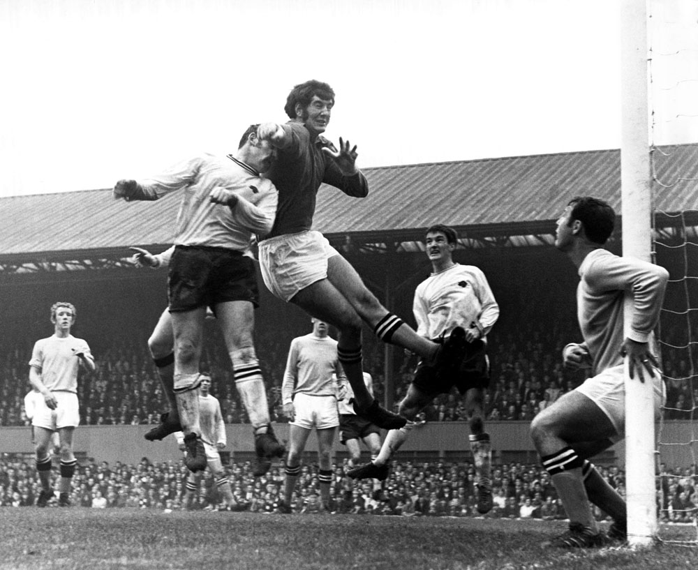 Joe Corrigan punches the ball clear from the head of Derby County skipper Dave Mackay. Oct 1969.