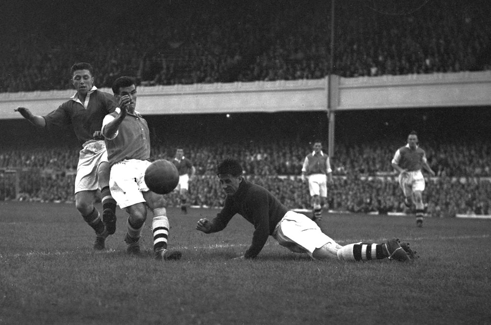 Former Liverpool player Tom McNulty tackles Arsenal's Peter Goring at Old Trafford, August 1952