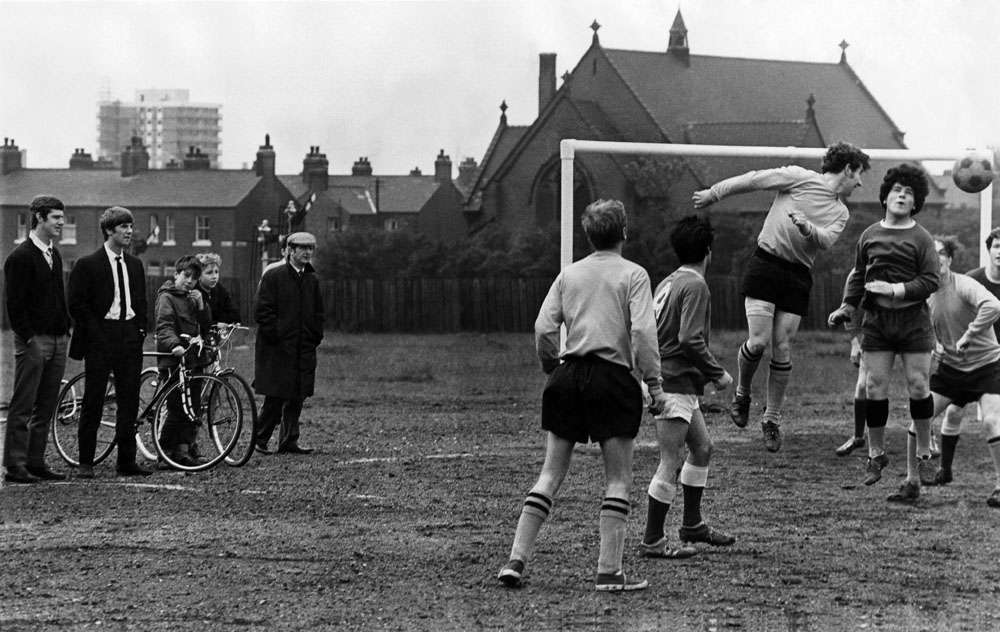 Brian Kidd and Stan Bowles, both left, watch some park football in Moston, October 1967