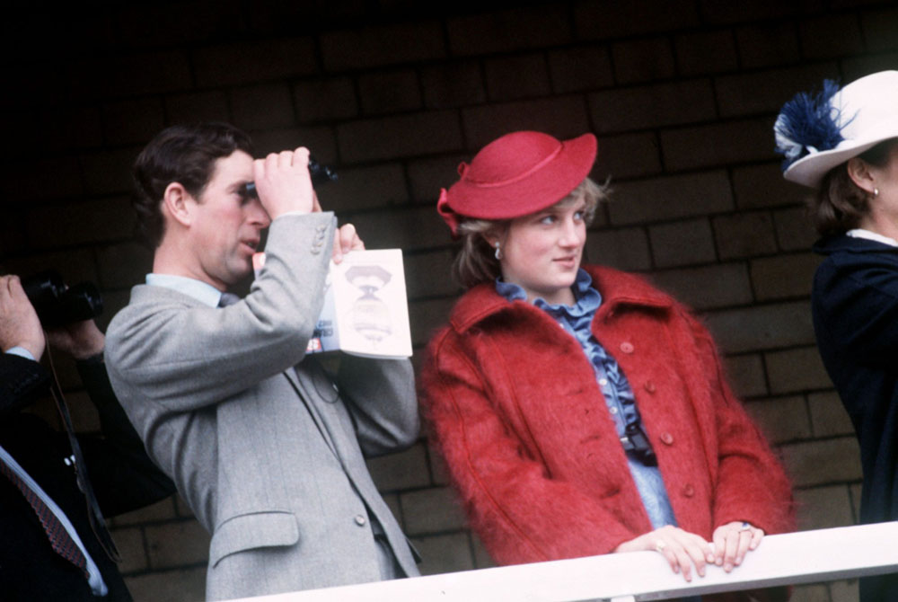 Prince Charles peers through binoculars at the Grand National, April 1982