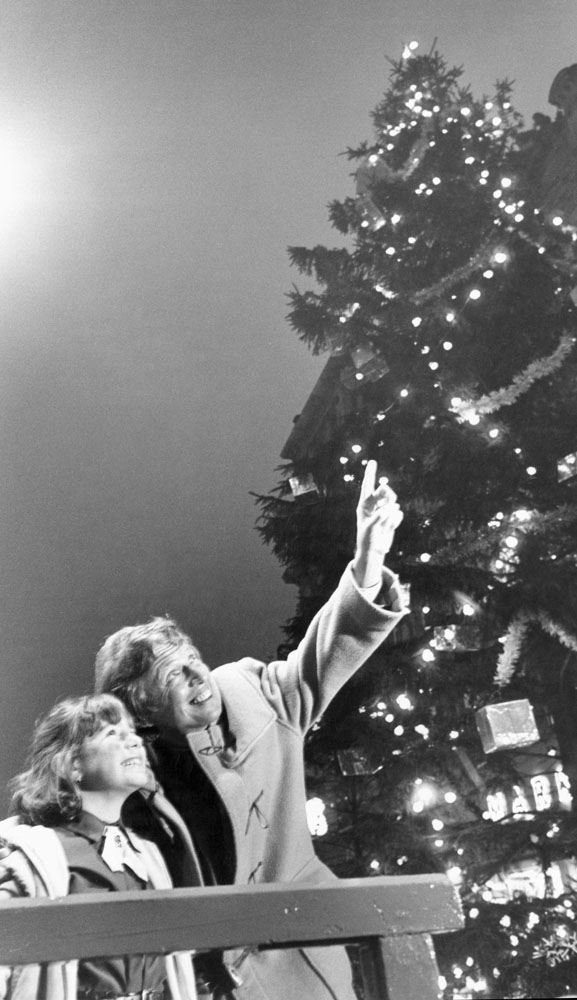 Tommy Steele and Claire Ryan, 6, from Speke marvel at the Christmas tree, December 1982