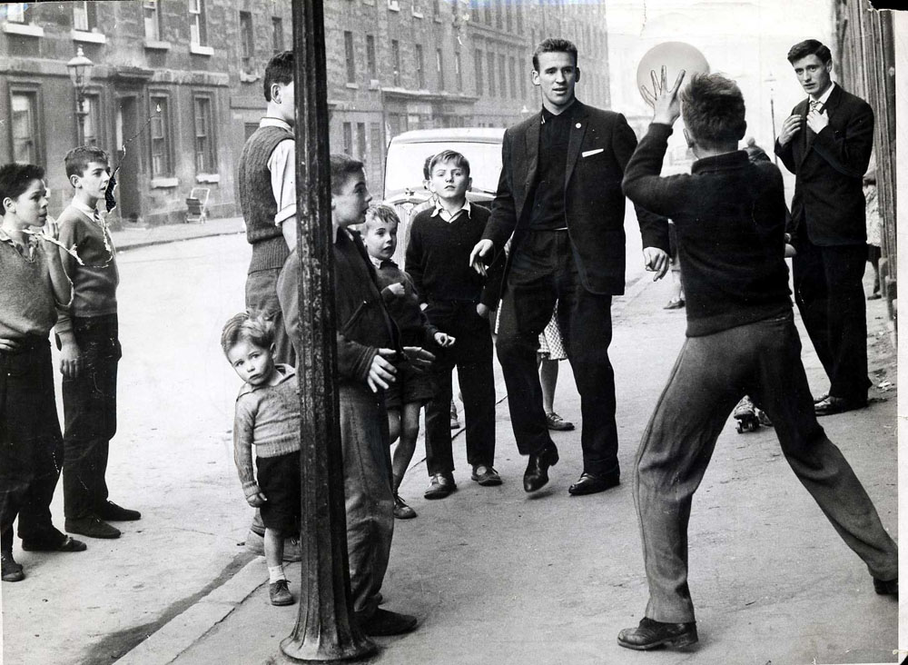 Crerand playing football with kids in street, January 1960