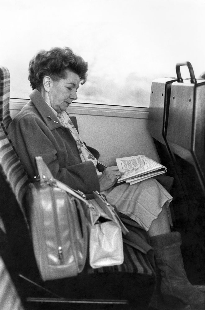 A crossword passes the time for Jean Alexander on the train to Manchester, December 1987