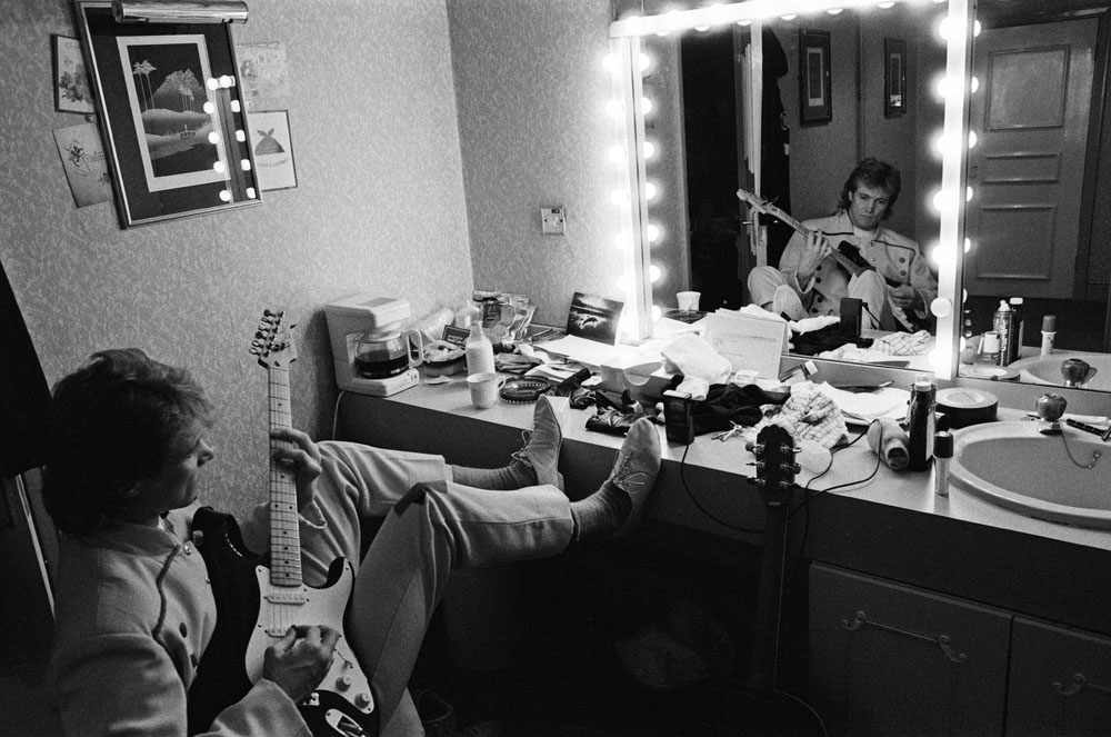 Bread star Peter Howitt strums the guitar backstage in Cinderella, January 1990