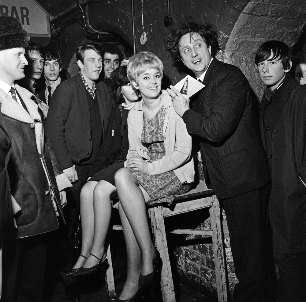 Ken Dodd signs his Cavern Club application on the back of Margaret Johnson, 19, from Anfield