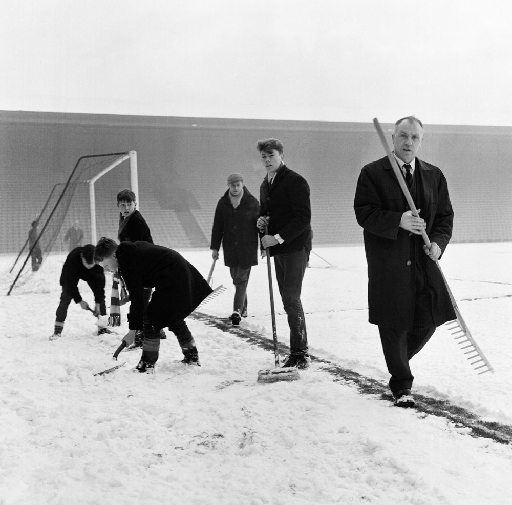 Bill Shankly helps rake snow off the lines at Anfield, December 1964