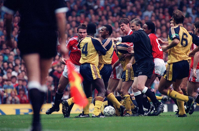 The referee stops a melee between United and Arsenal players at Old Trafford, December 1996