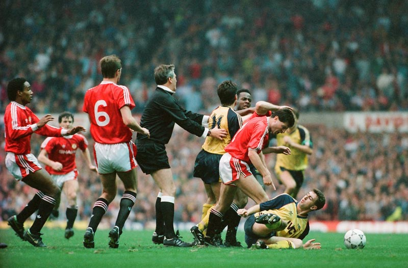 Referee Keith Hackett tries to control United and Arsenal players at Old Trafford, October 1990