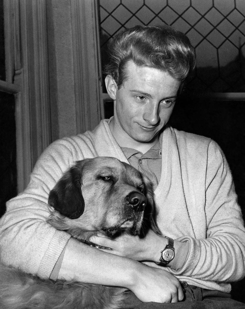 A downcast Denis Law relaxes with his landlady's dog after the six goals he scored against Luton were chalked off, January 1961