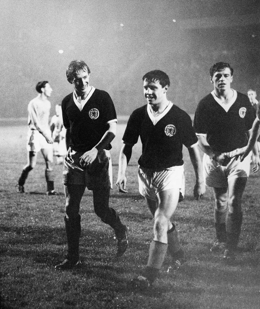 Four-goal Scotland hero Denis Law leaves the pitch with Willie Henderson and Eric Caldow, November 1962
