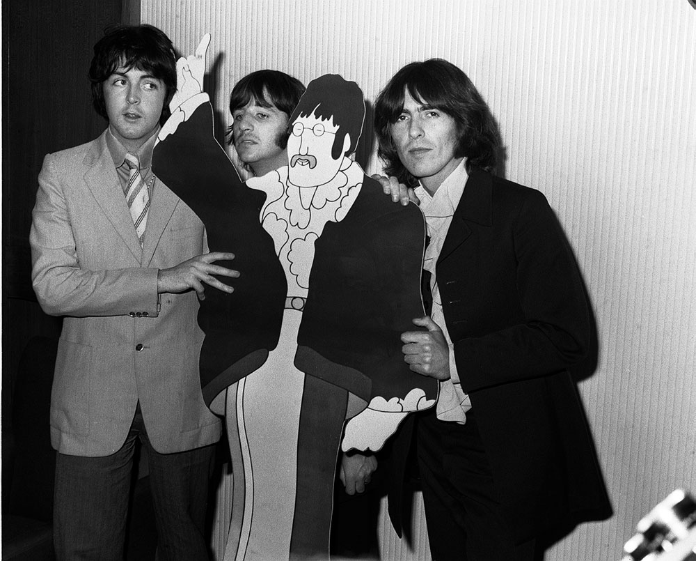Beatles Paul McCartney, Ringo Starr and George Harrison with a cardboard cut-out of John Lennon at the movie premiere of Yellow Submarine, July 1968