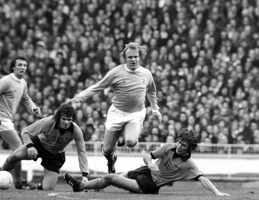 City forward Francis Lee hurdles two Wolves defenders, March 1974