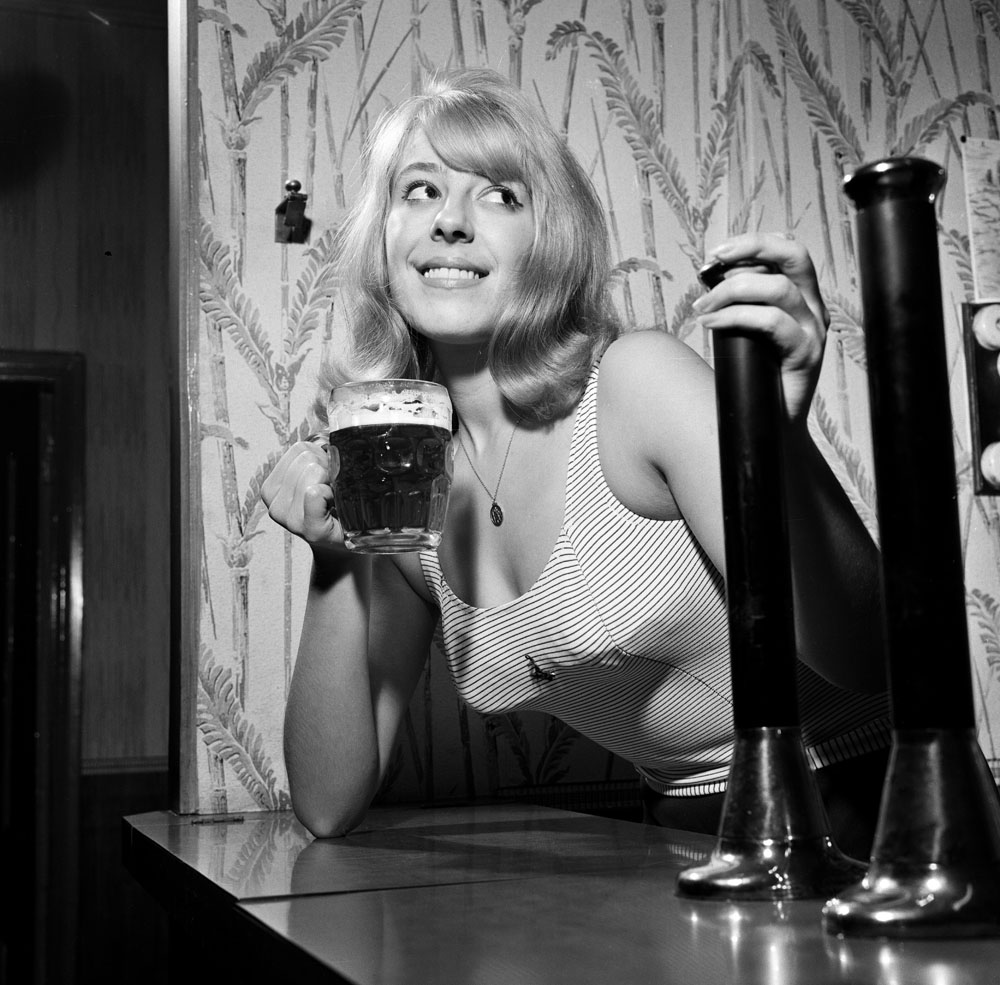 Julie Goodyear at her parents' pub before landing the role of barmaid Bet Lynch, December 1963