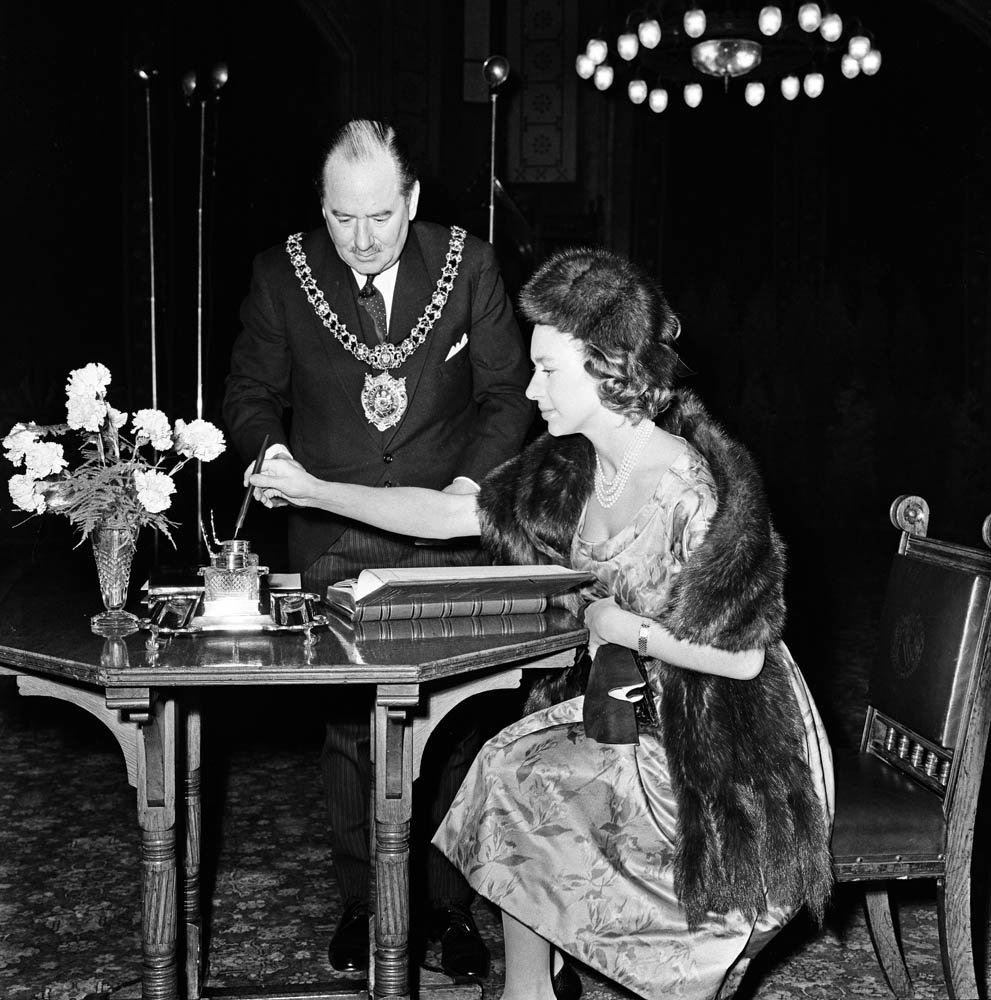 Lord Mayor Lionel Biggs watches Princess Margaret sign the Manchester visitors' book, March 1962