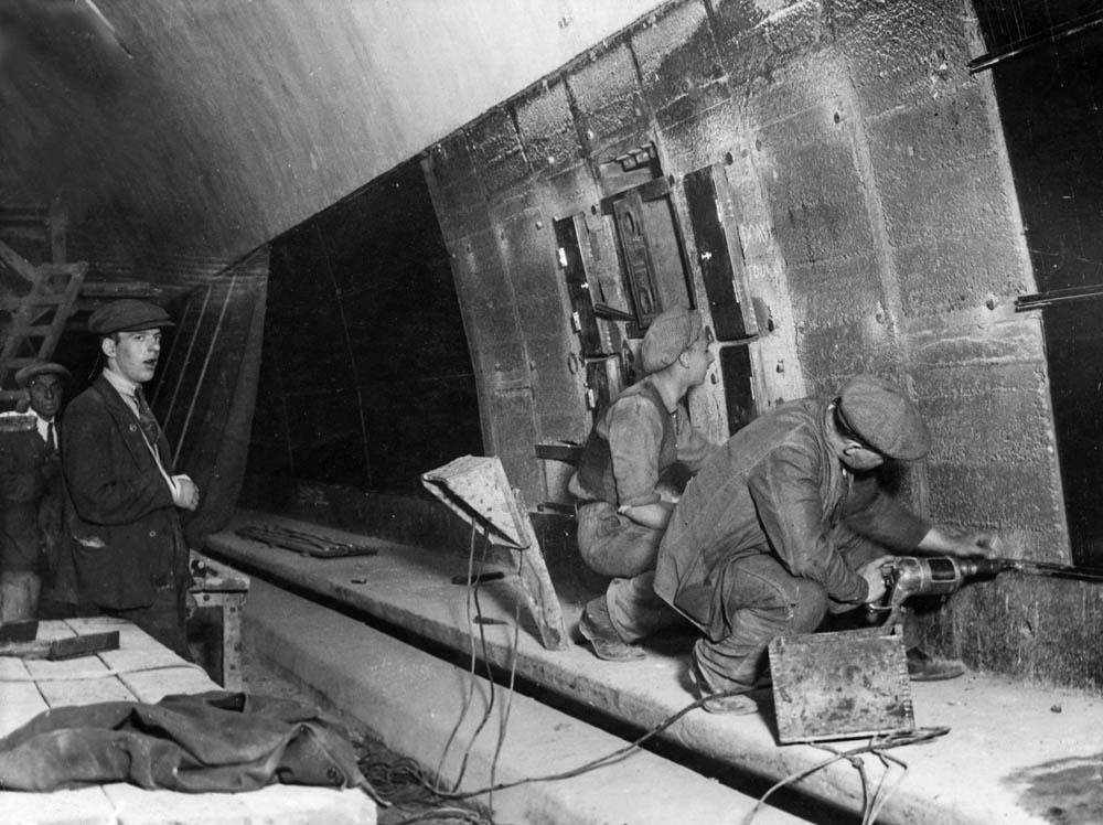 Workmen lining the Queensway Tunnel wall with glass, August 1933