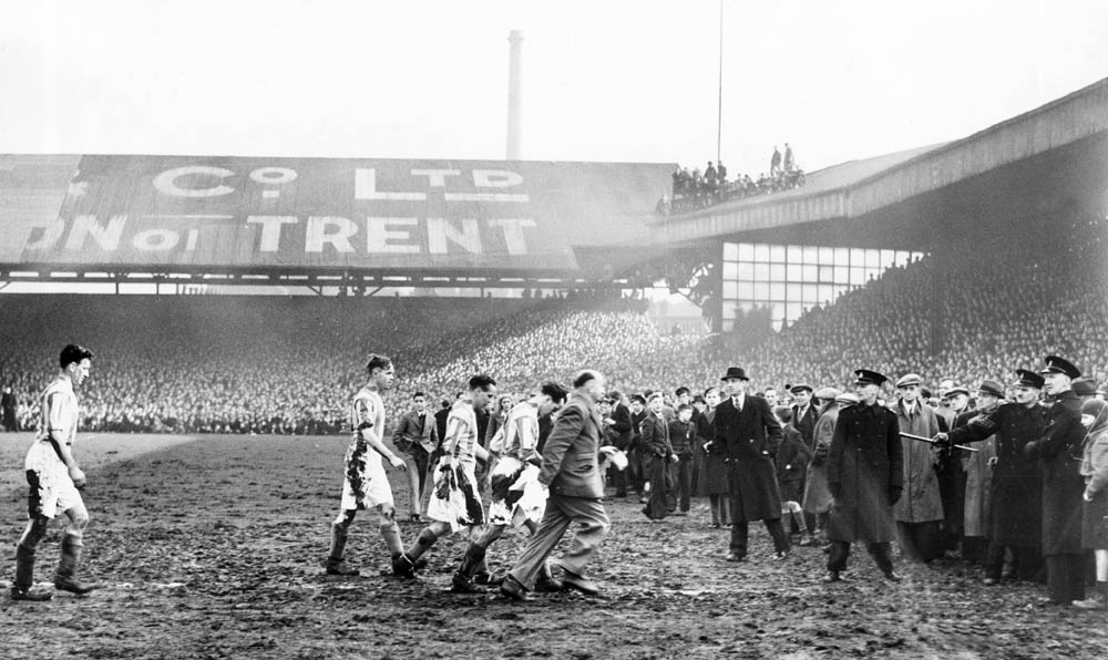 Players leave the pitch after spectators were crushed in the FA Cup match against Stoke, March 1946