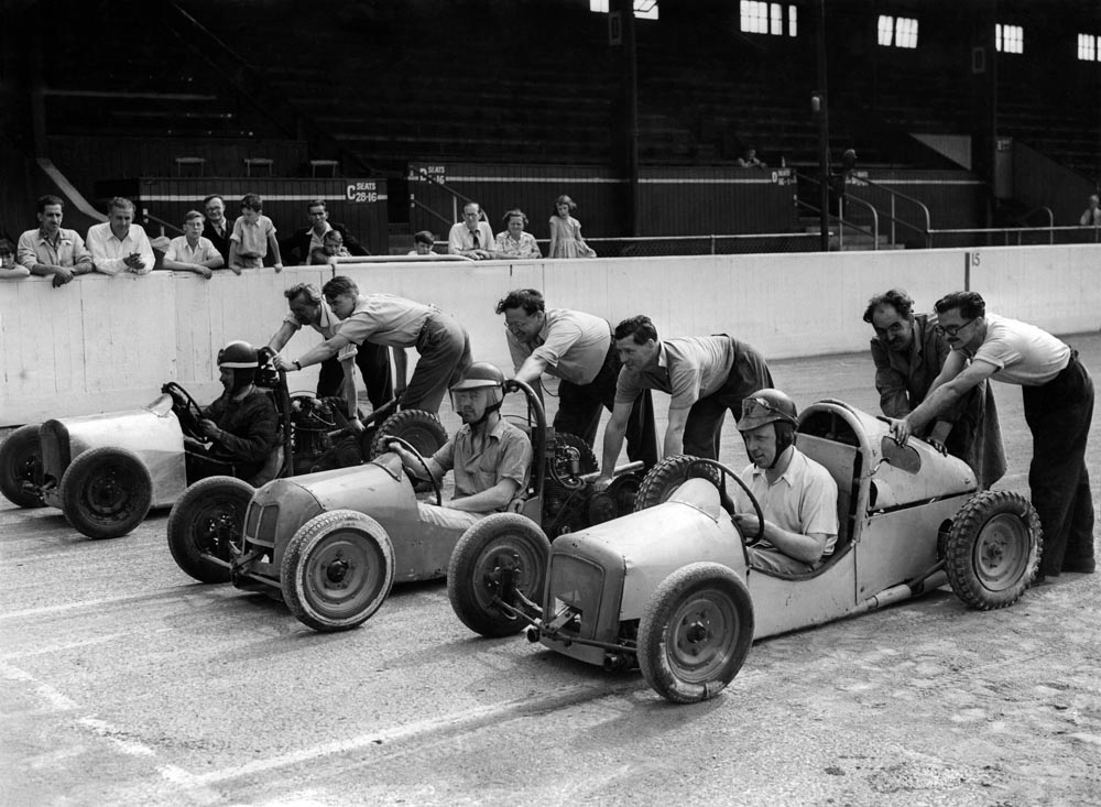 Midget racing cars line up at the Belle Vue track, August 1955