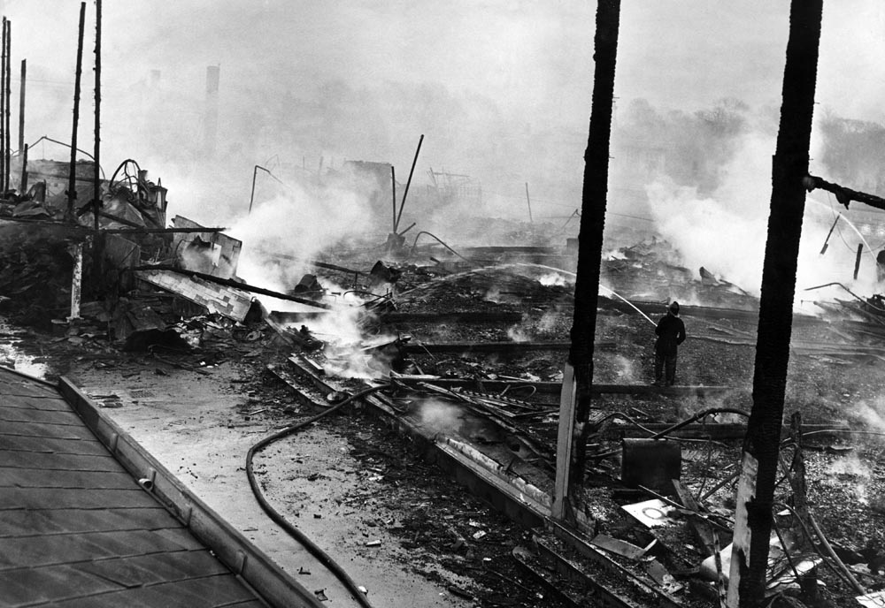 Firemen dowse the wreckage of the Cumberland Suite, October 1964