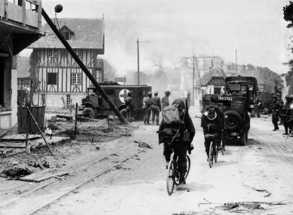 British troops advance inland through a French village, June 1944