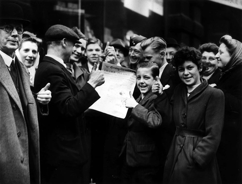 A crowd gathers round a newspaper seller in Manchester for news of D-Day, June 1944