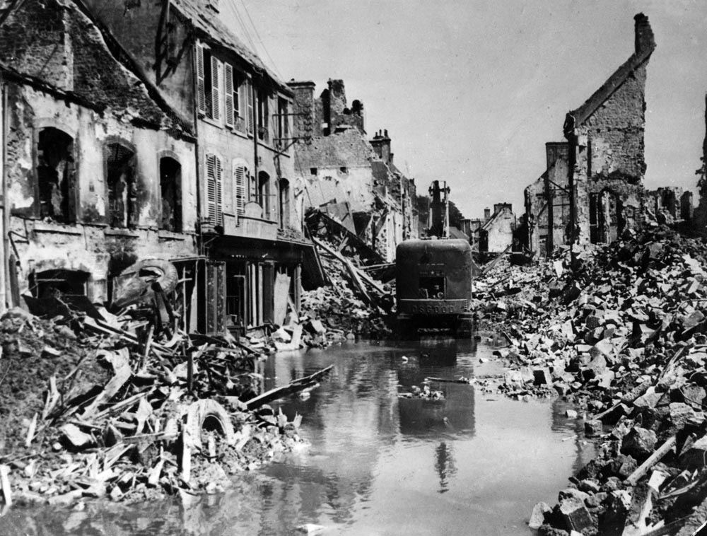 A mechanical shovel clears debris from the road in the destroyed town of Valognes, June 1944